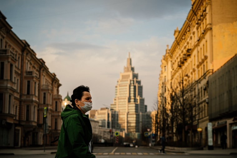 Image: A woman wearing a face mask walks in a deserted street in central Moscow