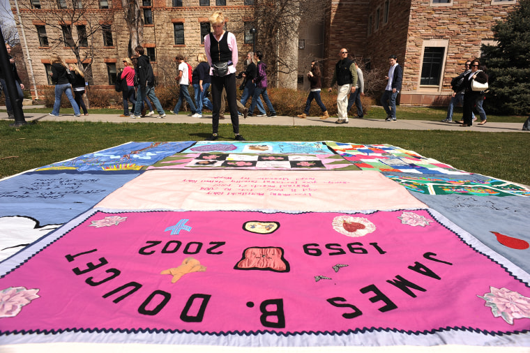 (HR) Gert McMullin looks at some of the quilts that are on display on the green grass outside of Norlin Library on the University of Colorado campus in Boulder. She was one out of the two first volunteers that started the AIDS Memorail Quilt project in Sa