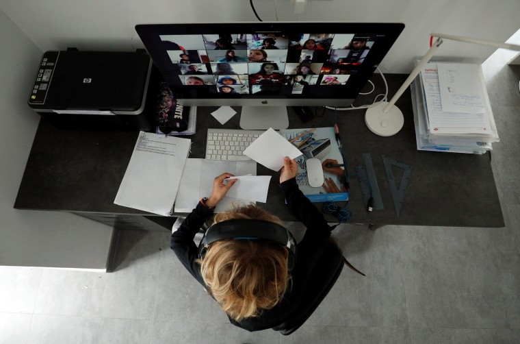 Image: A student takes classes online with his companions using the Zoom APP at home