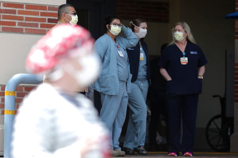Image: Nurses stand in a hospital doorway watching a nurses?EUR(TM) protest for personal protective equipment at UCLA Medical Center, as the spread of the coronavirus disease (COVID-19) continues, in Los Angeles