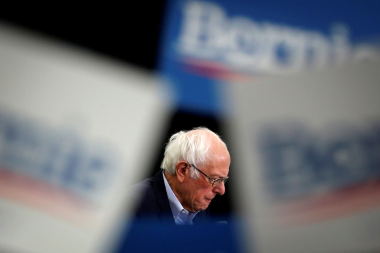 Image: Democratic U.S. presidential candidate Senator Bernie Sanders is seen as supporters wave signs as he speaks at a campaign rally in Milford