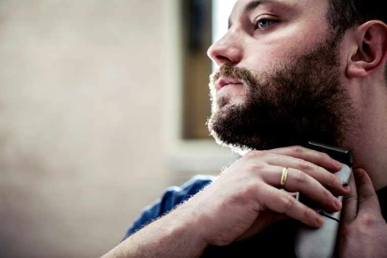 Young man shaving beard