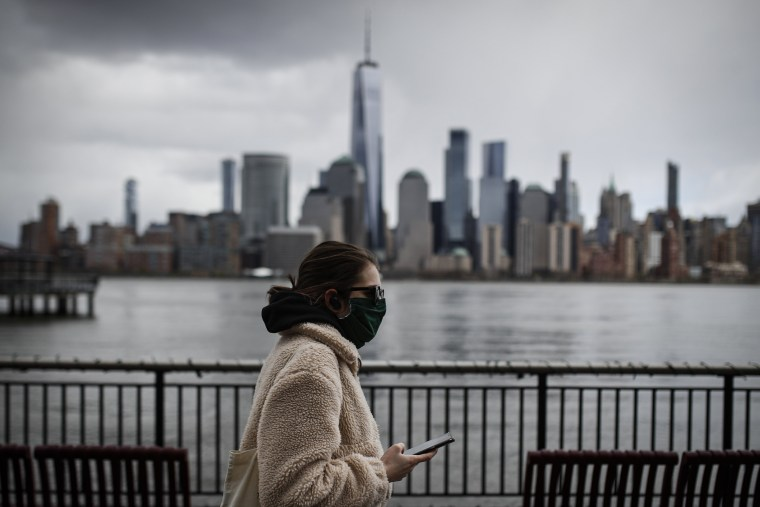 Image: A pedestrian wearing a mask holds her mobile phone in Jersey City, N.J.