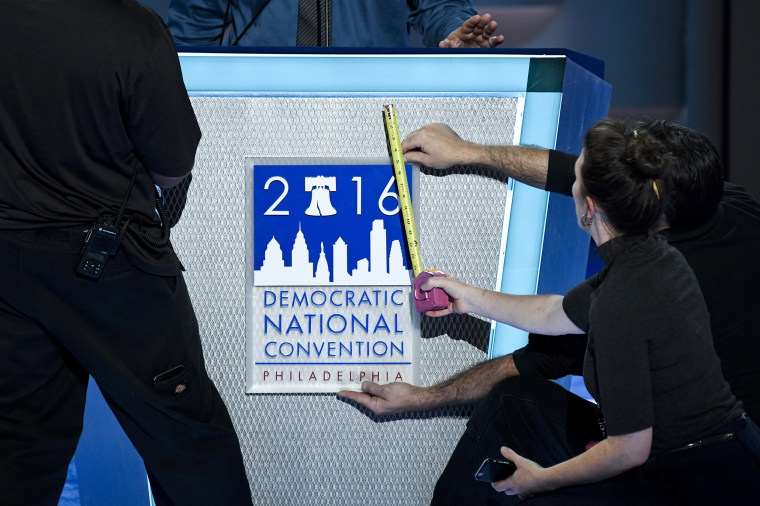 Image: Stage hands affix the DNC logo to the podium at the Democratic National Convention in Philadelphia
