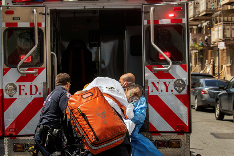 Image: New York City Fire Department and Emergency Medical Technicians lift a man after moving him from a nursing home into an ambulance