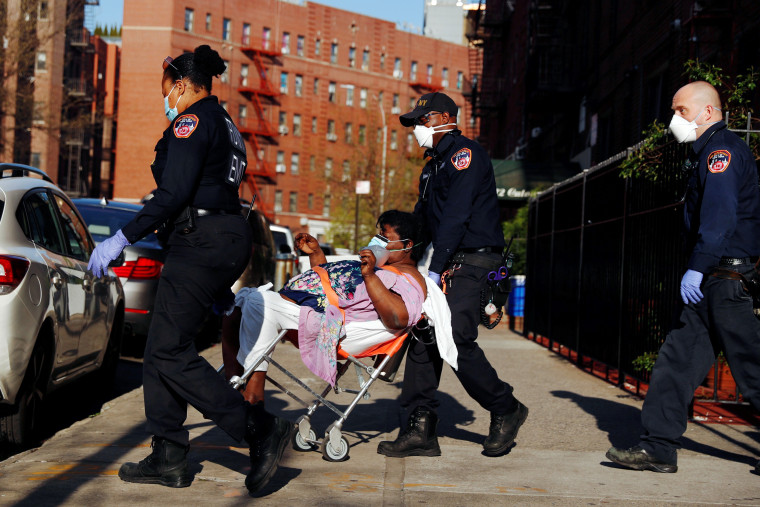 Image: A New York City Fire Department (FDNY) Emergency Medical Technician (EMT) wearing personal protective equipment assist a woman who was having difficulty breathing during ongoing outbreak of the coronavirus disease (COVID19) in New York