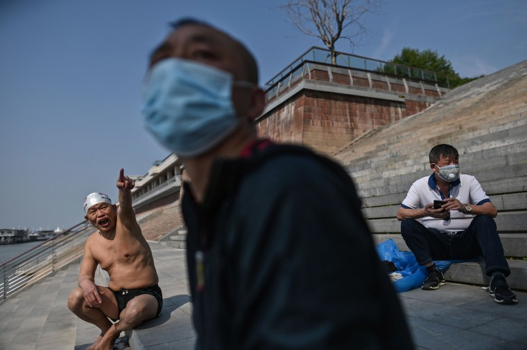 Image: A man wears a face mask as people gather along the Yangtze river in Wuhan, China's central Hubei province