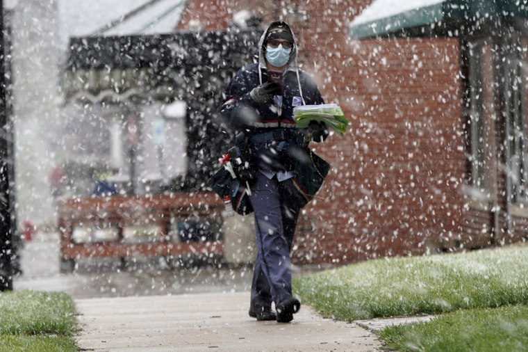 A mail carrier wears a face mask during a spring snow storm in Lincoln, Neb., on April 16, 2020.