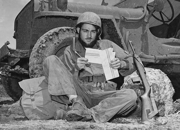 Propped against the wheel of his jeep, S/Sgt Dale Blakeslee of Carson City, Mich., uses a leisure minute to fill out the personal information form on his war ballot, on June 11, 1944 in the Mariana Islands.