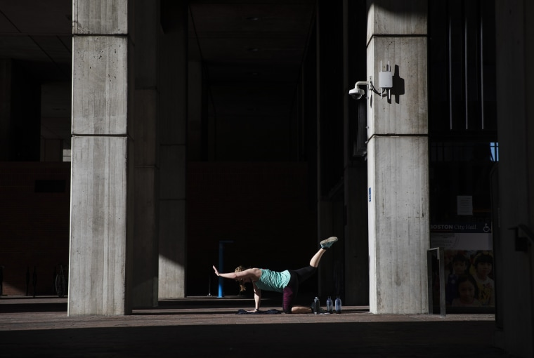 Unable to work out at her gym since it closed due to coronavirus, a woman exercises in a quiet corner at the entrance to City Hall in Boston on March 21, 2020.