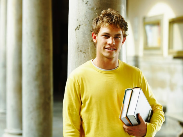 Male college student carrying books on campus