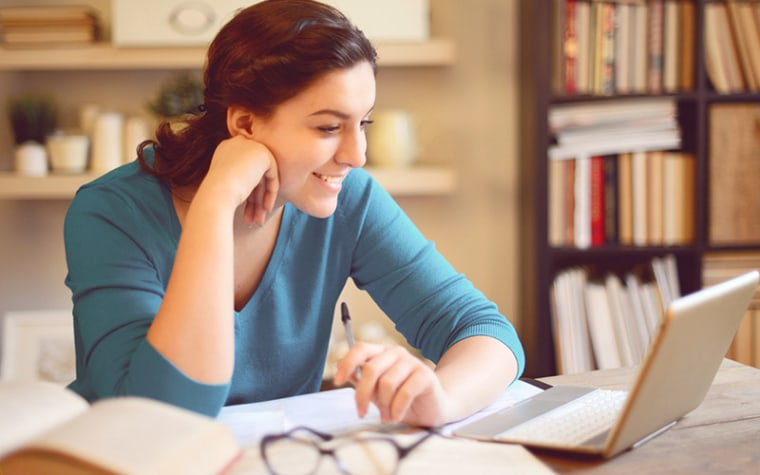 College aged girl in blue shirt working at computer