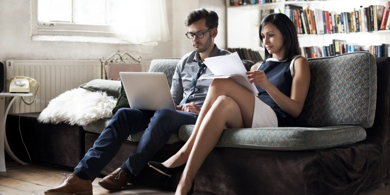 Couple sitting on sofa working