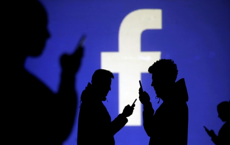 Image: People on phones next to a Facebook logo projection on March 28.