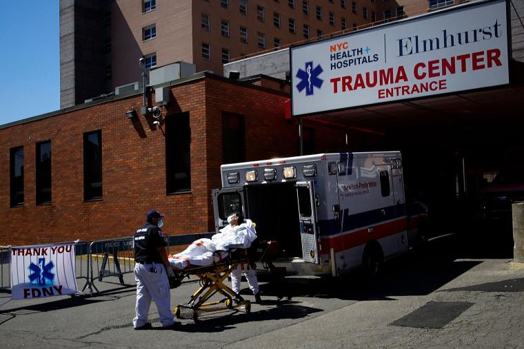 Image: Paramedics wheel a patient into Elmhurst Hospital during outbreak of coronavirus disease (COVID-19) in New York