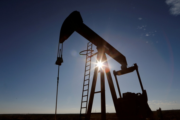 The sun is seen behind a crude oil pump jack in the Permian Basin in Loving County