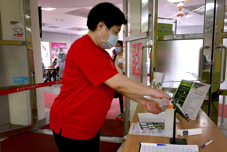 Image: A woman sanitizes her hands before going into a sports center in Taipei. Hand sanitizers are made available in many buildings and businesses in Taiwan.