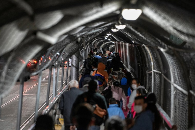"""Image: Migrants in the """"Remain in Mexico"""" program walk on the Paso del Norte International Bridge to reschedule their immigration hearings amid the coronavirus disease (COVID-19) outbreak in Ciudad Juarez, Chihuahua, Mexico"""