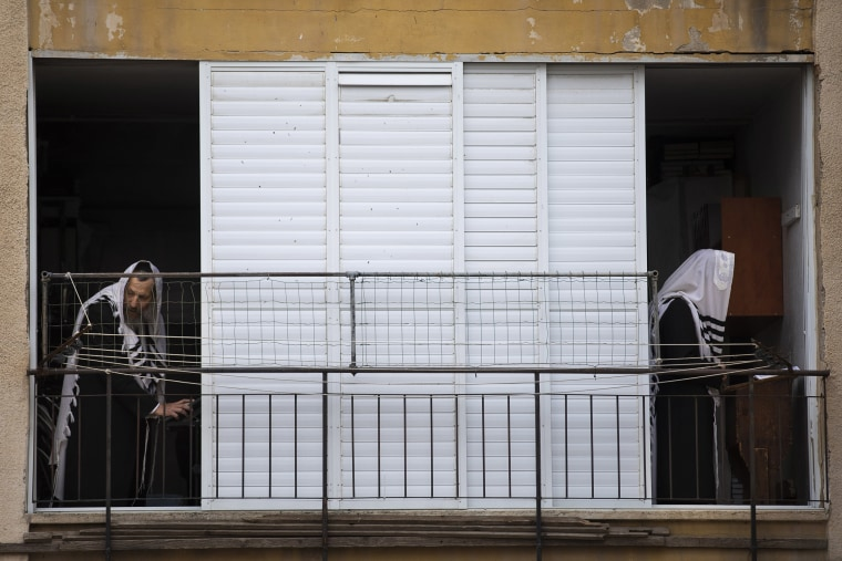 Image: Ultra-Orthodox Jews pray a morning prayer at their house as synagogues are closed following the government's measures to help stop the spread of the coronavirus, in Bnei Brak,
