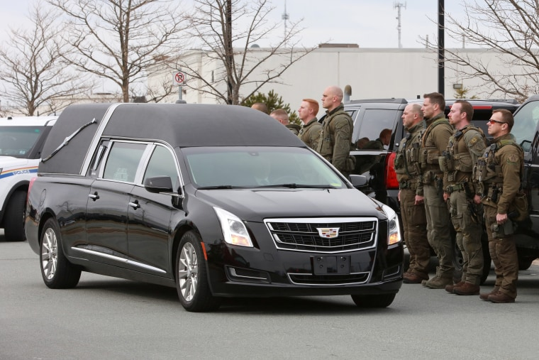 RCMP officers stand as a hearse carrying the body of Constable Heidi Stevenson passes in Dartmouth