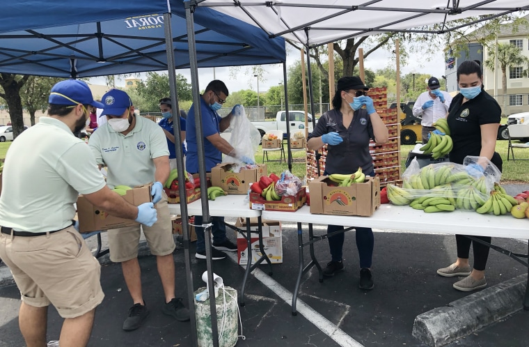 Volunteers distribute food at an event by Food Share in Doral, Fla.