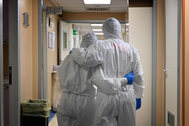 Image: Doctor Marco (R) and nurse Manu, wearing protective gear react at the end of their shift in a corridor of the level intensive care unit, treating COVID-19 patients, at the San Filippo Neri hospital in Rome