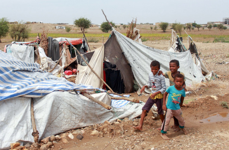 Image: Yemeni children play next to damaged tents due to torrential rain in a makeshift camp for the displaced in the northern Hajjah province