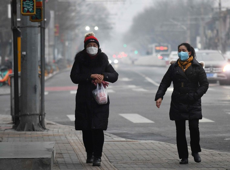 Image: Women wear face masks to protect against COVID-19 on a polluted day in Beijing
