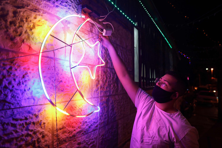 Image: A Palestinian youth wearing a protective mask amid the COVID-19 pandemic hangs decorative lights on a wall in east Jerusalem