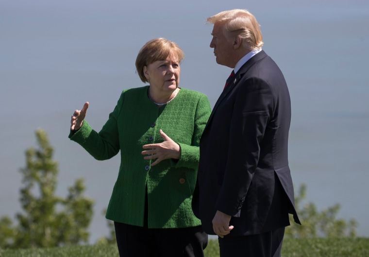 Image: German Chancellor Angela Merkel confers with US President Donald Trump following the family photo session during the G7 Summit in La Malbaie, Canada