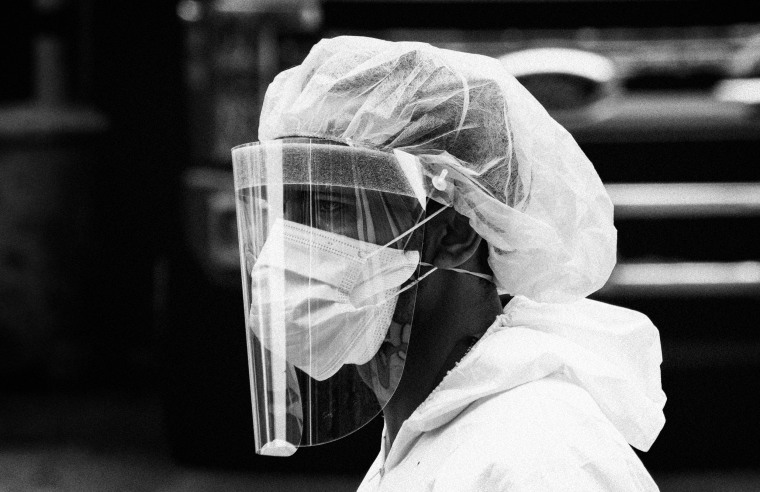 Image: A health care worker wearing personal protective equipment leaves Elmhurst Hospital in Queens, N.Y., on April 5, 2020.