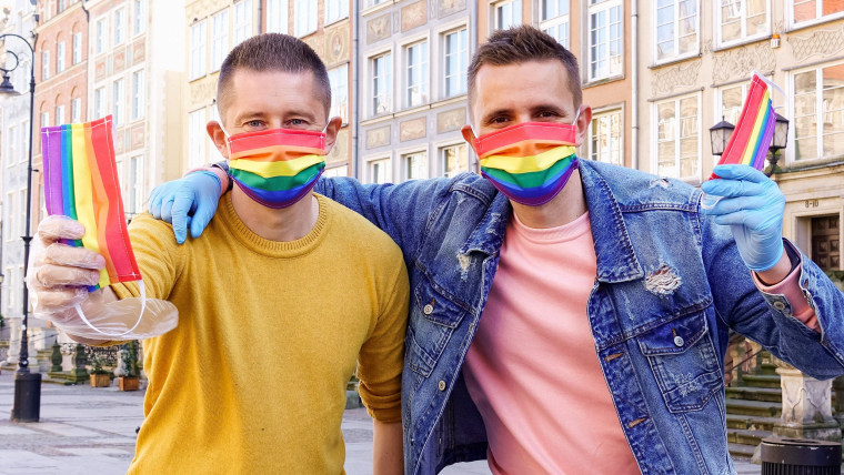 Image: Gay couple Dawid Mycek and Jakub Kwiecinski pose with the rainbow-patterned face masks on a street in Gdansk