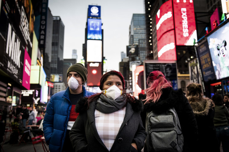 Image: Pedestrians wearing face masks walk through New York's Times Square on March 12, 2020.