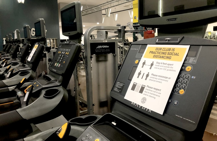 A gym preparing to reopen in Georgia with social distancing signs on the equipment.