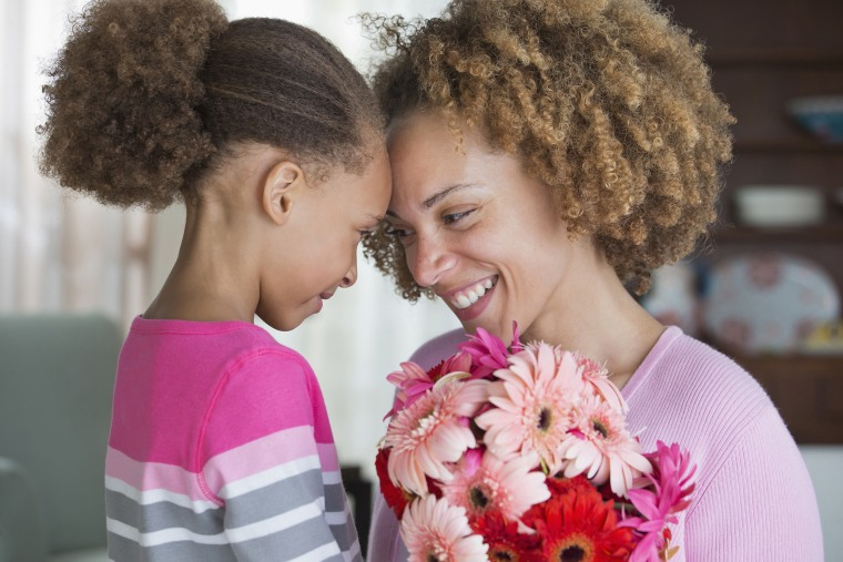 Image: Black mother and daughter holding bouquet of flowers