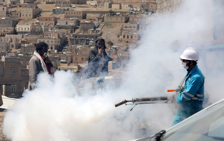 Image:  People cover their faces as a health worker fumigates a residential area in the battle against the coronavirus outbreak on the outskirts of Sanaa, Yemen