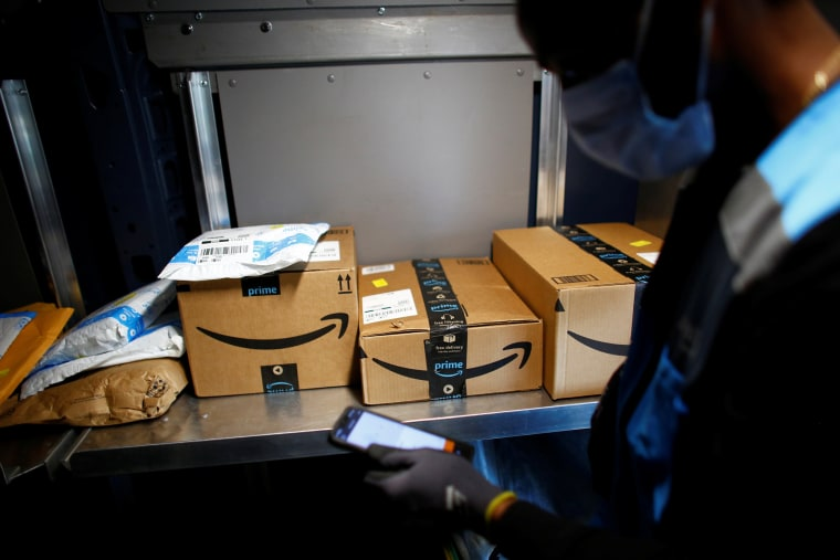 Image: An Amazon worker delivers packages