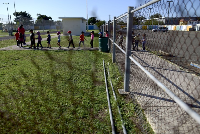 Kindergarten students from the Martin G. Brumbaugh School are led by their teacher to the race track for exercise in Santa Isabel, Puerto Rico on Feb. 4, 2020.