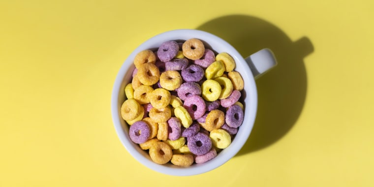 Colorful Corn Rings In Cup On Yellow Background
