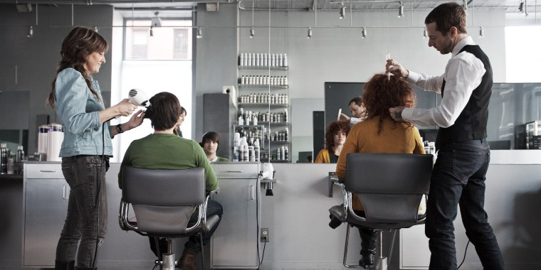 clients getting haircuts in salon