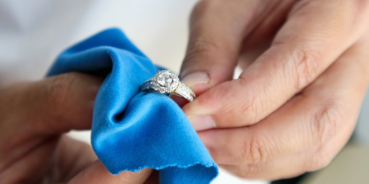 hand polishing and cleaning jewelry diamond ring with micro fiber fabric
