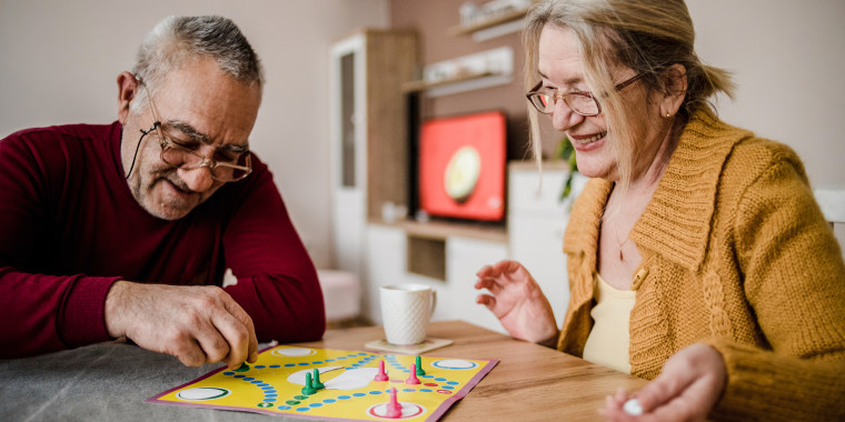 An older couple plays board games