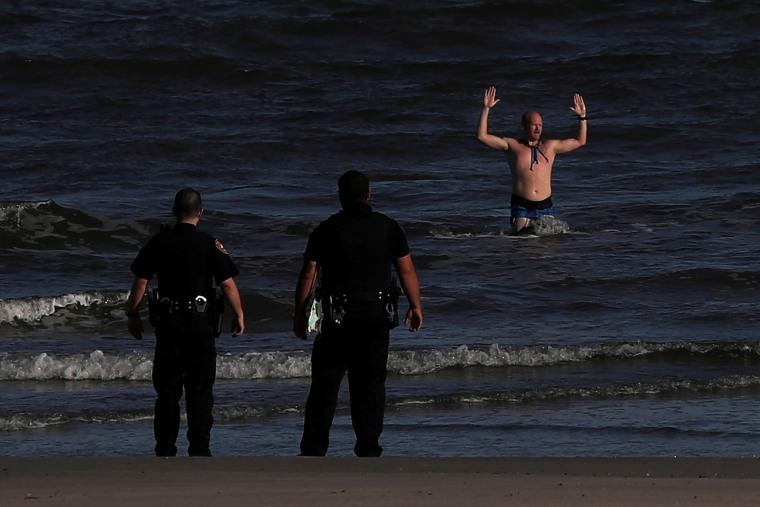 Image: Man exits Galveston Beach with arms raised during coronavirus disease (COVID -19) pandemic in Galveston, Texas