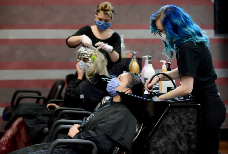 Image: Customers wear masks at a salon in Marietta, Ga., after the state reopened businesses and restaurants after restrictions to curb the spread of coronavirus on April 24, 2020.