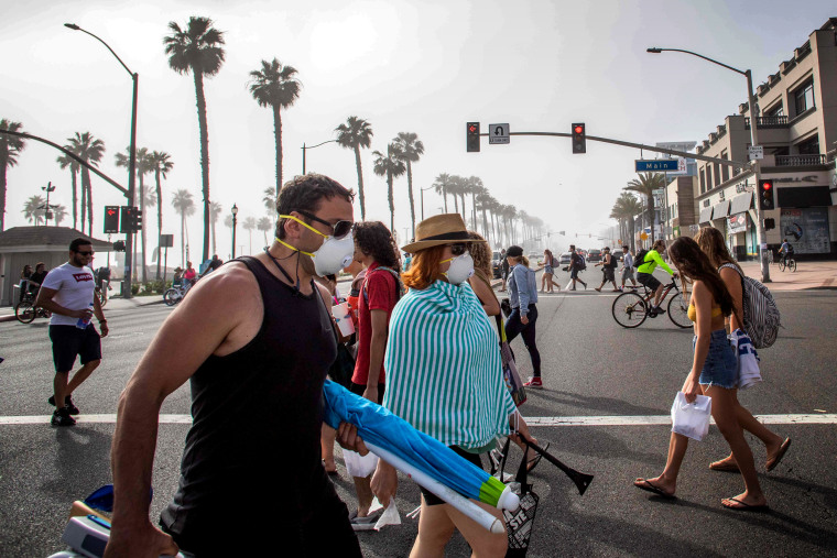 Image: Pedestrians cross the street near Huntington Beach, Calif., on April 25, 2020. Orange County beaches remain open amidst other social distancing measures to curb the spread of coronavirus.