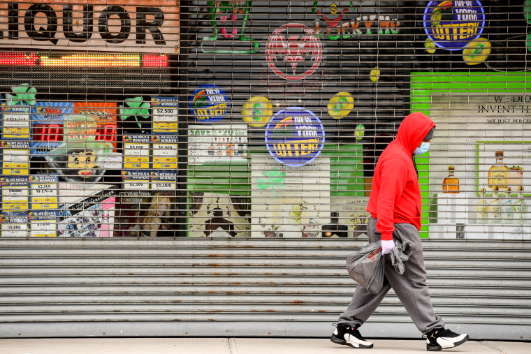 Image: A pedestrian walks past closed storefronts in Central Islip, N.Y., on March 25, 2020.
