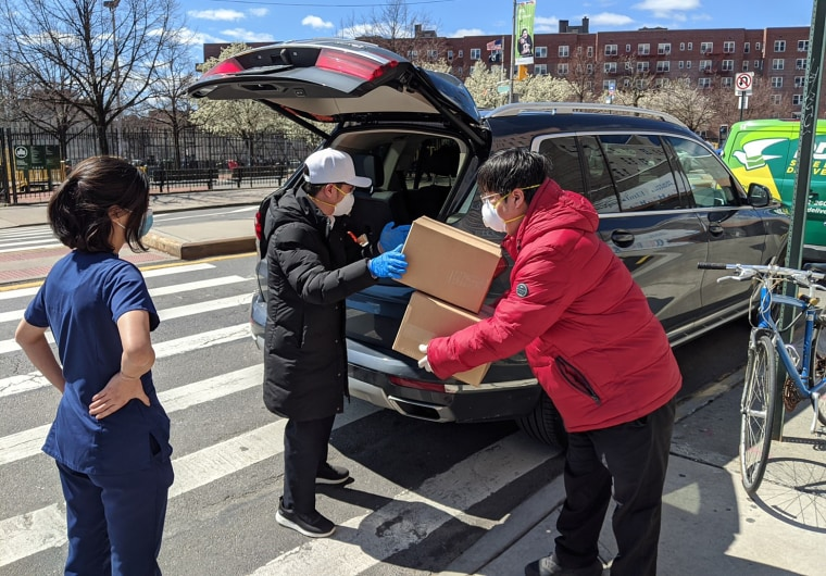 Joey Chiang, president of the Taiwanese Chamber of Commerce of New York, and others help unload boxes of masks they donated to Elmhurst Hospital in Queens.