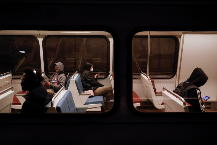 A passenger looks at her cell phone while riding in a Metro train car, as Mayor Muriel Bowser declared a State of Emergency due to the coronavirus disease (COVID-19), at the Metro Center underground train station in Washington