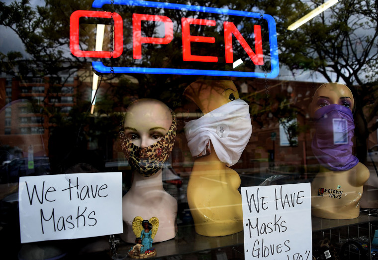Image: Mannequin heads wear masks in the window of a small boutique advertising availability of masks, gloves, and other pandemic necessities amid the Coronavirus outbreak in Arlington