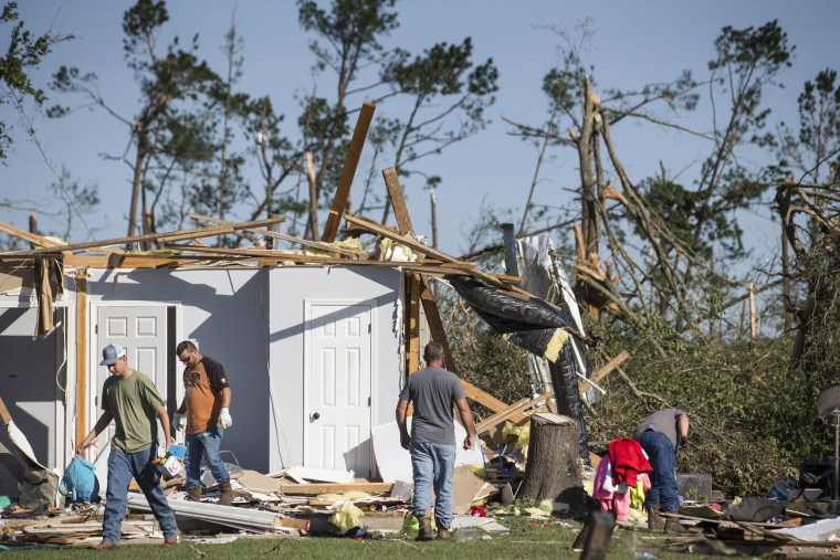 Residents sift through the rubble of a home on April 23, the day after a tornado ripped through the area in Onalaska, Texas.